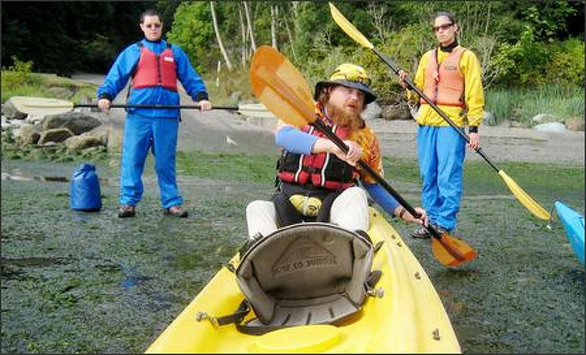 Guide A.J. Dauel demonstrates paddling to Chris Eccles and Celia Nieto. Hiring an outfitter is a good option for novices, as swells and currents can be nasty.