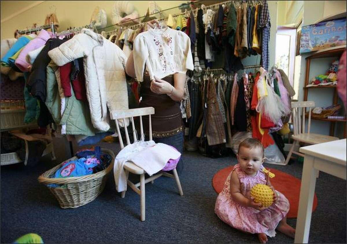 Sara Radke looks at a sweater for her daughter Bebe Izabella Radke, foreground, at Sugarlump.