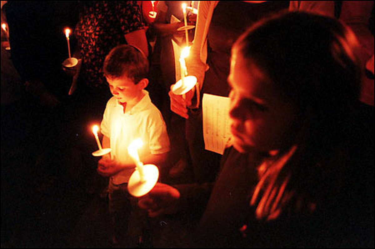 Thomas Riley, 6, and Emma Dorland, 8, burn candles with hundreds of mourners at St. James Cathedral in Seattle, Wash. after a multi-faith service including leaders of Juddiasm, Islam and Christianity.