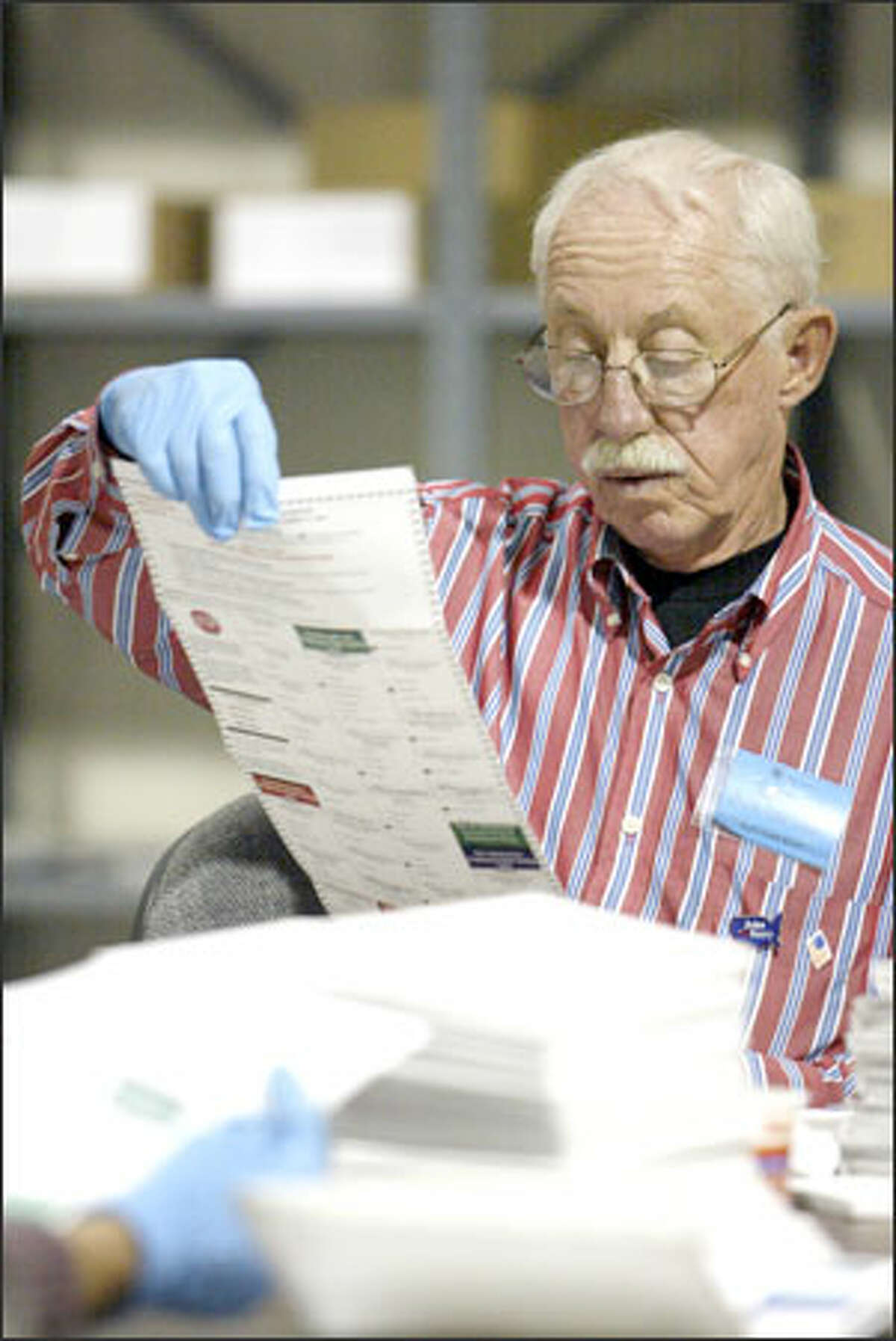 Bob Brown of the Mail Ballot Operations Satellite in South Seattle inspects absentee ballots. If a party is not checked, votes on that ballot for partisan races are not counted.