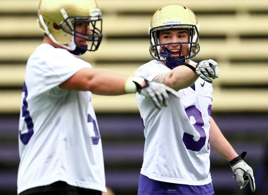 Cort Dennison, right, calls out to a teammate during the first spring practice for the University of Washington football team on Tuesday, March 29, 2011 at Husky Stadium in Seattle. Photo: Joshua Trujillo / Seattlepi.com