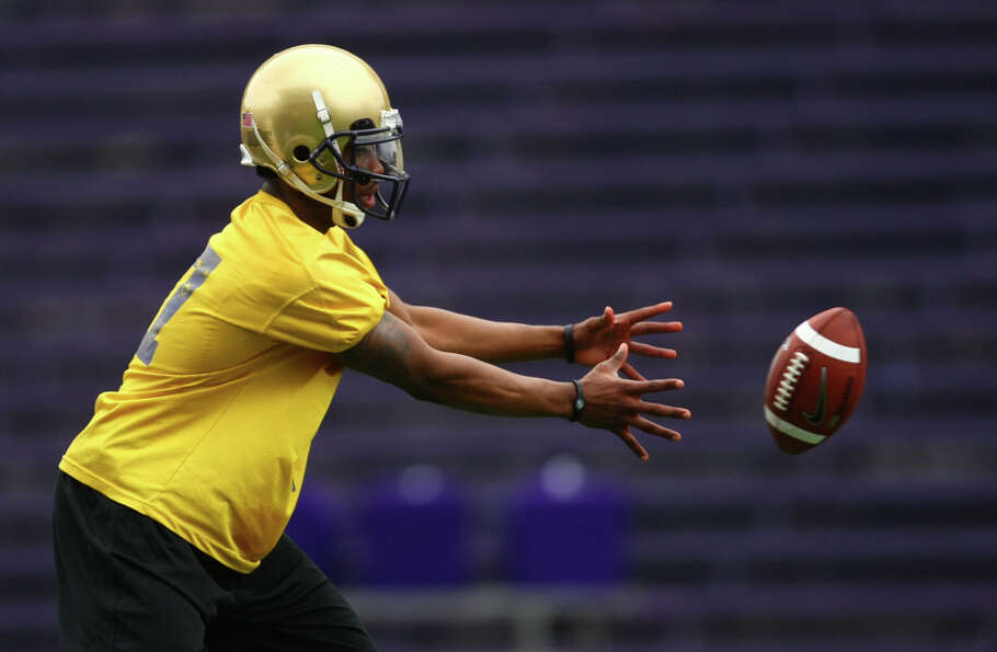 Quarterback  Keith Price takes the snap during the first spring practice for the University of Washi