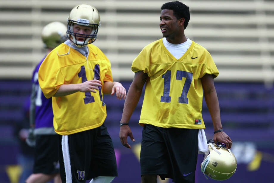 Quarterbacks Keith Price, center, and Thomas Vincent (14) take a break during the first spring practice for the University of Washington football team on Tuesday, March 29, 2011 at Husky Stadium in Seattle. Photo: Joshua Trujillo / Seattlepi.com