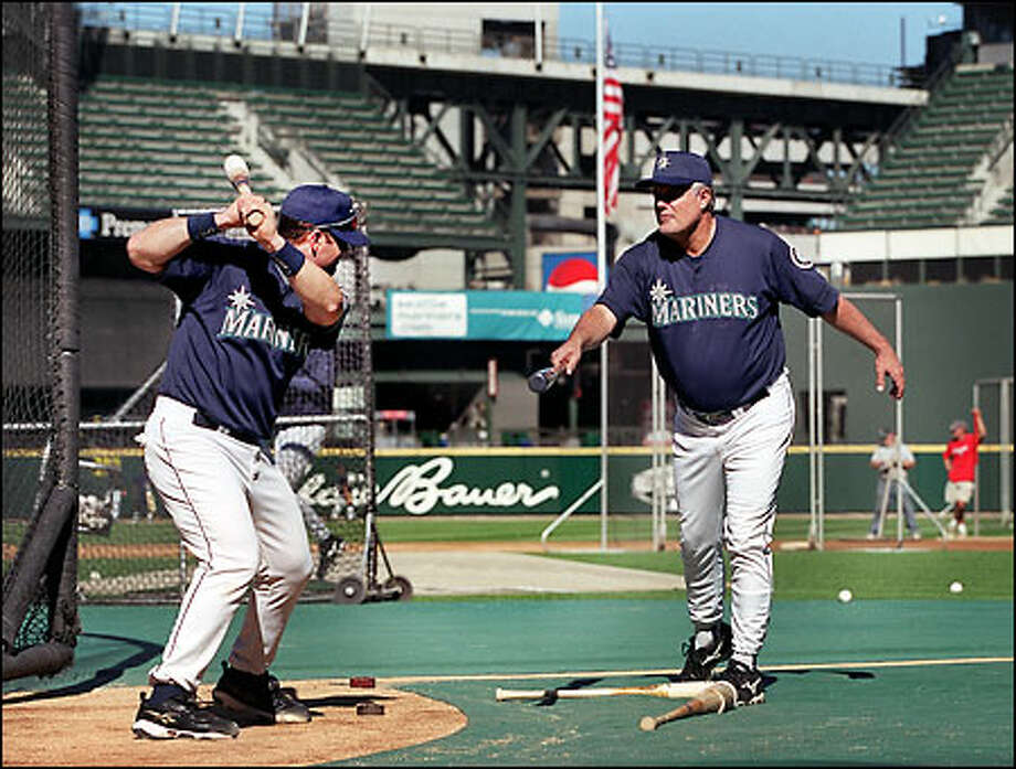 With the U.S. flag at half-staff behind them, Mariners manager Lou Piniella works with Edgar Martinez during the team's first practice at Safeco Field since play was suspended Tuesday. Photo: Dan DeLong, Seattle Post-Intelligencer / Seattle Post-Intelligencer