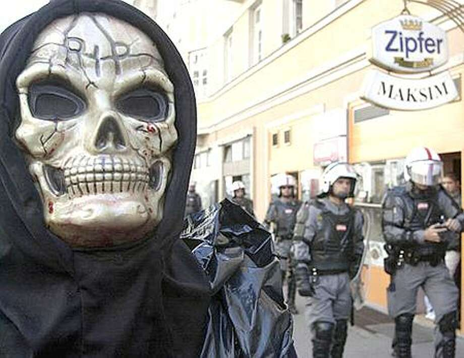 A masked demonstrator is seen on Sunday, Sept. 15, 2002, during an anti-globalization demonstration in Salzburg, Austria, ahead of a European Economic summit starting  Monday at the city's congress center. (AP Photo/Darko Bandic) Photo: Associated Press / Associated Press