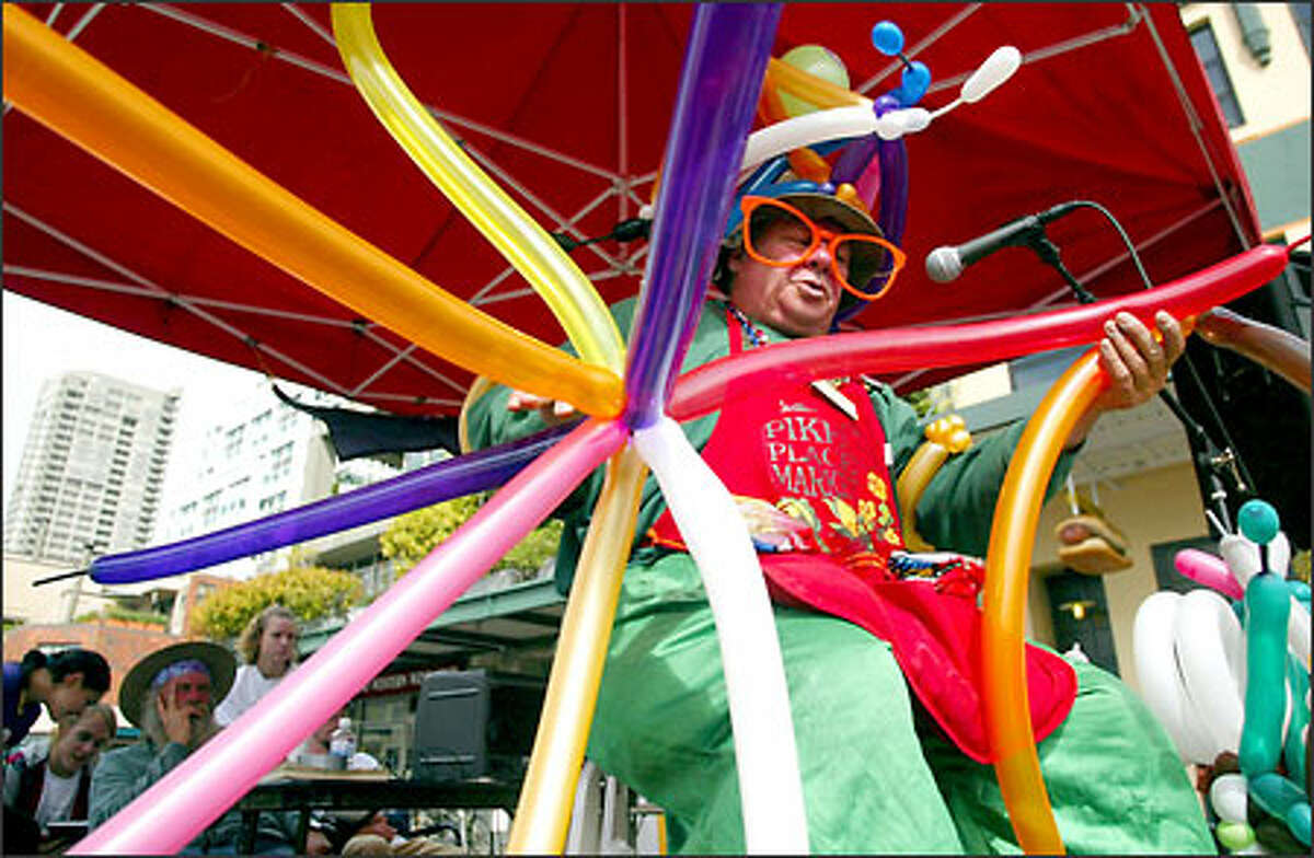 Twister Thomas, aka Thomas Farrell, makes an elaborate balloon sculpture on one of three stages at the Pike Place Market during the second annual Buskers' Festival.