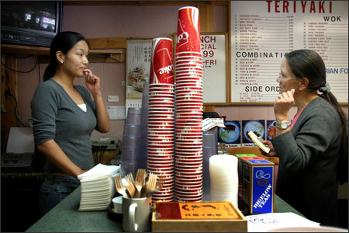 Gena Moon, left, takes the order of customer Sharon Cross at the Yummy Yummy Teriyaki store south of downtown Seattle, which is in the path of the planned monorail station.