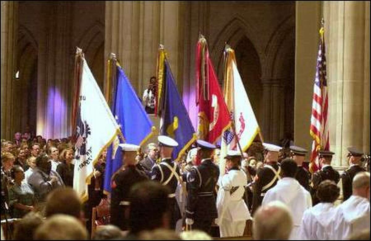 An honor guard presents the colors before services at the National Cathedral in Washington, D.C., this morning. Many Americans sought comfort in hymns and prayers after this week's terrorist attacks.