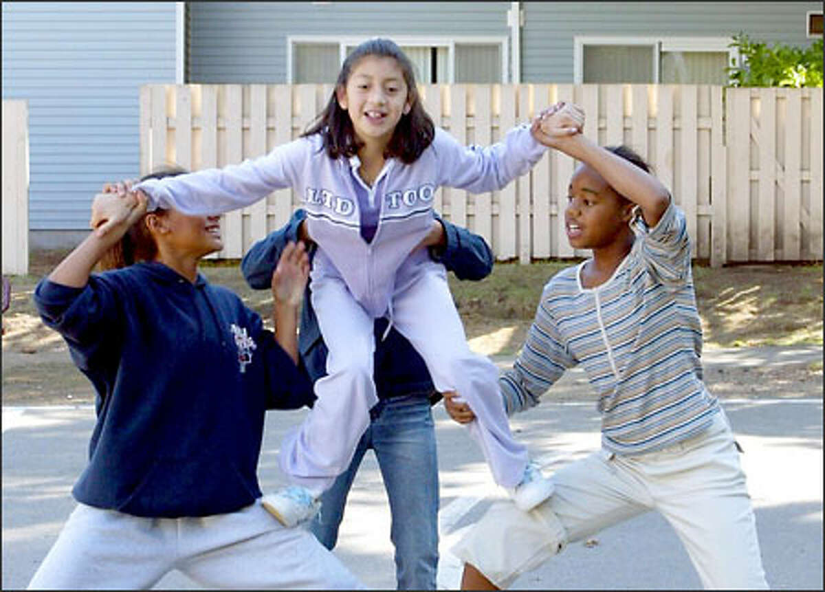 From left, Jhamelia Bates, 12, Gabby Quezada, 12, Britney Brewster, 11 (in back, face not showing), and Rashell Rensvold, 11, go though cheerleading drills.