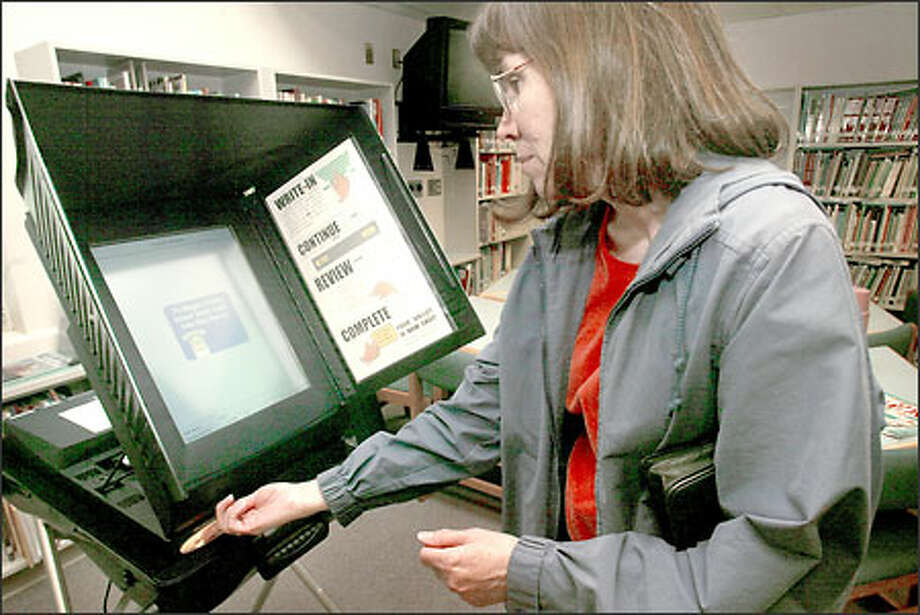 Esther Pickard inserts an activation card into a touch-screen voting machine at Martha Lake Elementary School in Snohomish County, where the machine made its Washington state debut. Photo: Grant M. Haller, Seattle Post-Intelligencer / Seattle Post-Intelligencer