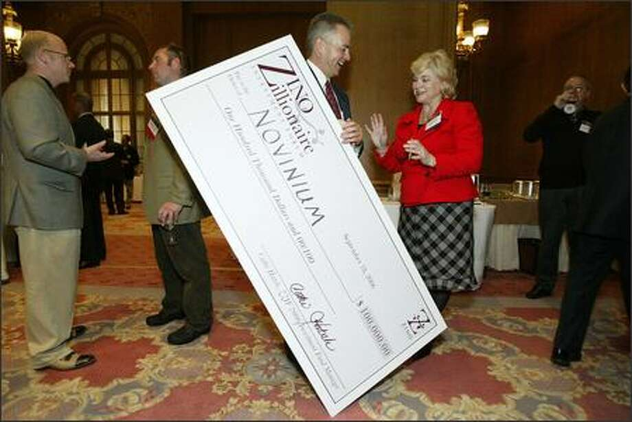 The Zino Society's Cathi Hatch congratulates Novinium CEO Glen Bertini on winning the top prize at a forum Monday at Seattle's Fairmount Olympic Hotel. Photo: Mike Urban, Seattle Post-Intelligencer / Seattle Post-Intelligencer