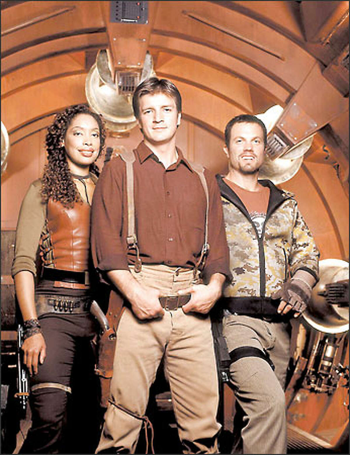 """In Fox's """"Firefly,"""" Gina Torres, left, Nathan Fillion and Adam Baldwin play characters surviving by their wits on a spaceship."""