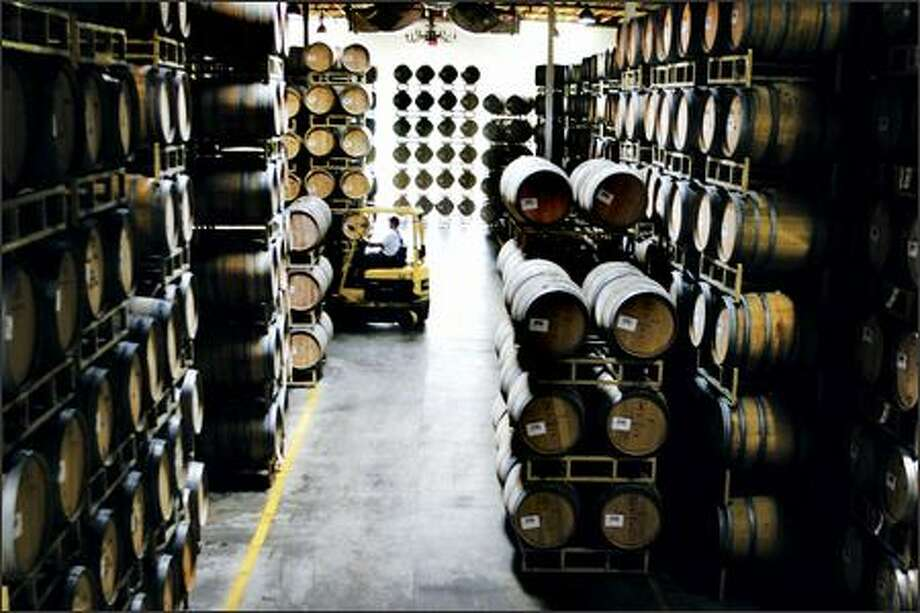 Oak barrels are moved in the cellar at Chateau Ste. Michelle winery in Woodinville, one of the Washington firms that expects more sales if Congress approves a trade agreement with South Korea. Photo: Meryl Schenker, Seattle Post-Intelligencer / Seattle Post-Intelligencer