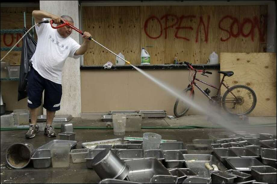 Restaurant owner Francisco Paco Vargas powerwashes pans in Galveston, Texas, on Friday. Photo: Associated Press / Associated Press
