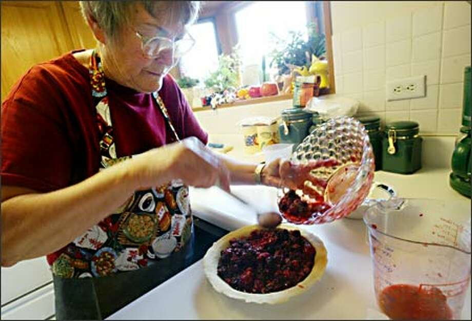 Carol Lagasca practices making the Merry Marionberry Pie she'll enter in the Puyallup Fair, where she's won first place in every pie category. At the top are her many ribbons. Photo: Dan DeLong, Seattle Post-Intelligencer / Seattle Post-Intelligencer
