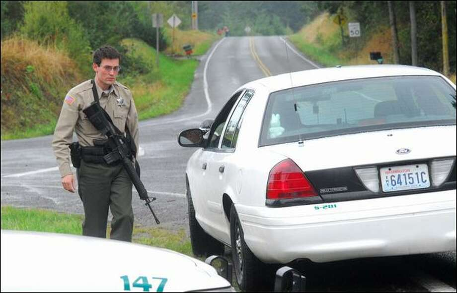 Clallam County Sheriff's Deputy Ken Oien guards a crossroads seven miles from the site where a Forest Service officer was killed Saturday. (Keith Thorpe / Peninsula Daily News)