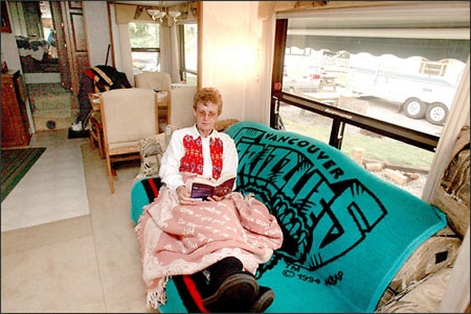 Janneke Cherniwshan enjoys the lap of luxury and all the comforts of home -- and a good romance novel -- in her fifth wheel at the Beachwood Resort in Birch Bay. Photo: Grant M. Haller, Seattle Post-Intelligencer / Seattle Post-Intelligencer