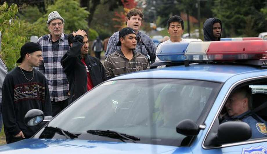 Neighbors look on at the scene of a shooting that left four people dead and another wounded Thursday in Seattle. (AP Photo/Elaine Thompson) Photo: Associated Press / Associated Press