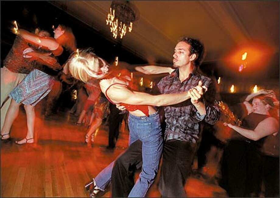 Vassili, right, leads Blair Bates around the dance floor at the Century Ballroom. Vassili started salsa dancing eight months ago and says it makes him feel sensual without being sexual. Photo: Loren Callahan, Seattle Post-Intelligencer / Seattle Post-Intelligencer