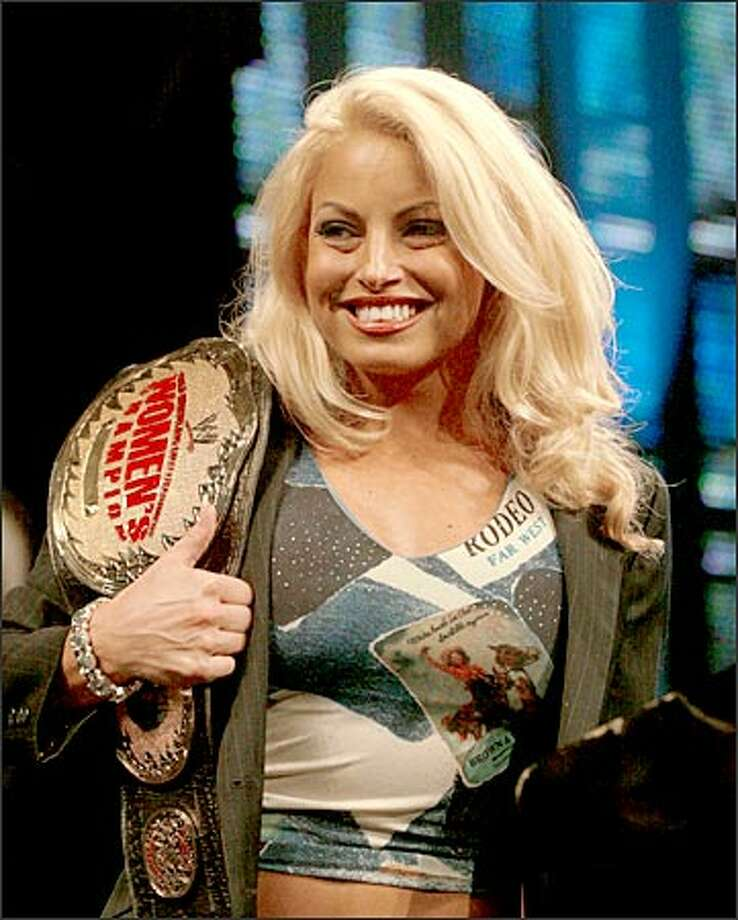 Trish Stratus shows off her Woman's Championship belt as stars of the wrestling world were introduced Tuesday morning to promote Wrestlemania XIX at EMP. Wrestlemania XIX will be held at Safeco Field on March 30, 2003. Photo: Grant M. Haller, Seattle Post-Intelligencer / Seattle Post-Intelligencer