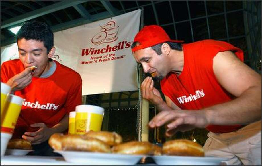 Richard Bustos, 19, left, and Ray Meduna of Mount Vernon pound 'em down in the Winchell's World Donut Eating Championship held Wednesday at the Los Angeles County Fair in Pomona. Photo: Grant M. Haller, Seattle Post-Intelligencer / Seattle Post-Intelligencer