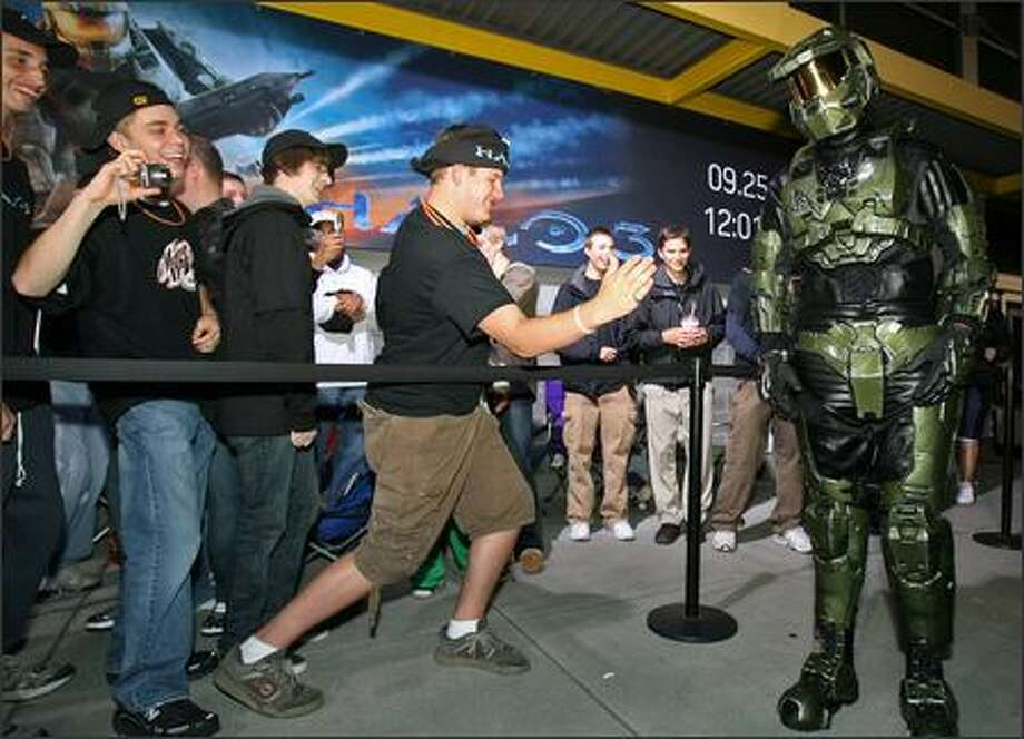 Gamer Michael Hutchinson, 17, from Maple Valley, tries to coax a high-five out of Master Chief. Hutchinson and other Halo fans line up at Best Buy in Bellevue on Monday to buy the latest edition of the Halo 3 video game, which was scheduled to go on sale at 12:01 Tuesday. Photo: Mike Urban, Seattle Post-Intelligencer / Seattle Post-Intelligencer
