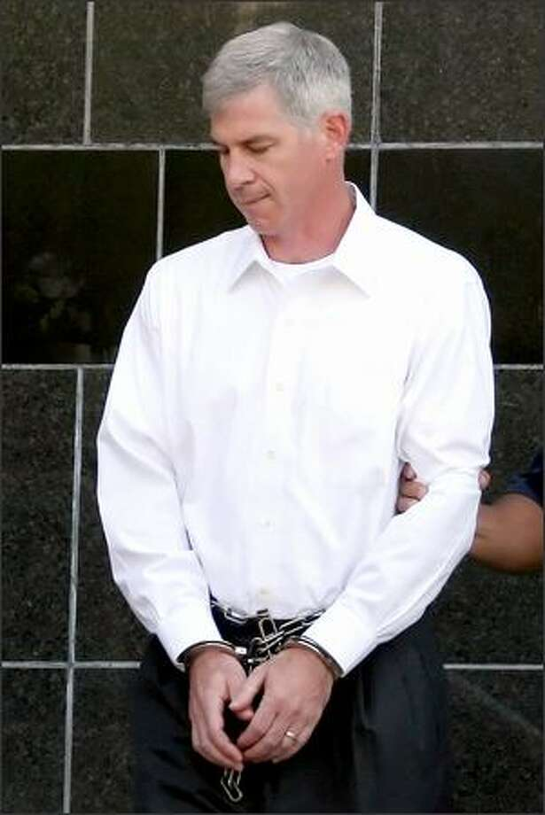Former Enron executive Andrew Fastow keeps his head down as he leaves the federal courthouse in Houston in chains after being sentenced to prison for six years Tuesday. Photo: Associated Press / Associated Press