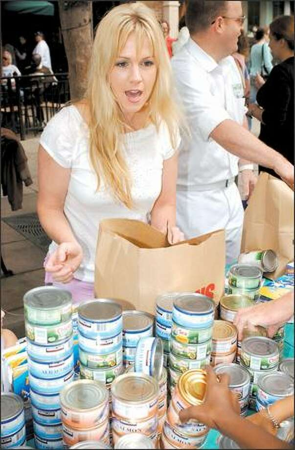 "Although she looks kinda bedraggled and a little like Tonya Harding (circa early 1990s), we have to admit: Jennie Garth looks adorable when she's helping people. Here, the ""What I Like About You"" star is packing groceries for the Angels in Action food drive (a volunteer-based community program) in Santa Monica, Calif., over the weekend. Photo: Associated Press / Associated Press"