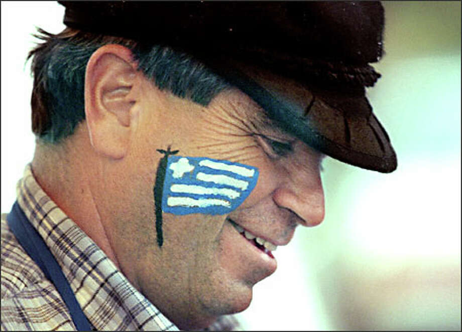 With the flag of Greece painted on his face, Steve Fatseas barbeques souvlakia, pork loin that's been marinated in Greek spices, at the St. Demetrios Greek Festival at the St. Demetrios Greek Orthodox Church in Seattle. Photo: Dan DeLong, Seattle Post-Intelligencer / Seattle Post-Intelligencer