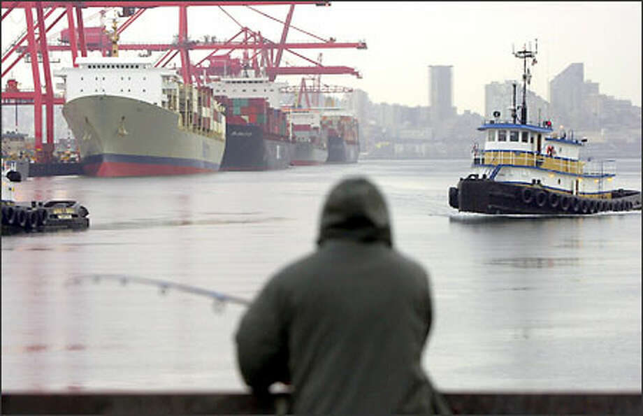 """A fisherman waits with his line in the water near Terminal 18, where dockworkers began loading and unloading cargo ships Sunday. """"There's some tough issues in negotiation that we need to go over, but hopefully they won't manifest themselves on the waterfront,"""" the association's Pacific Northwest manager Joseph Weber said in Seattle, where nearly 200 dockworkers began working on four cargo ships. Photo: Associated Press / Associated Press"""