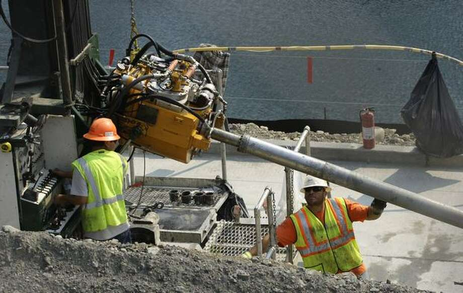 In this Sept. 23 photo, workers adjust a drill being used to strengthen the Howard Hanson Dam near Ravenswood. The dam began showing disturbing signs of vulnerability after a torrential rainstorm in January, and officials have been warning residents to buy flood insurance, stow valuables in safe places and be ready to flee. Residents face the all-too-real prospect that the river will gush past the leaky dam and swallow up their homes once the rainy season starts in November, devastating a heavily developed area in the Seattle suburbs that is a vital hub of commerce. (AP Photo/Ted S. Warren) Photo: Associated Press / Associated Press