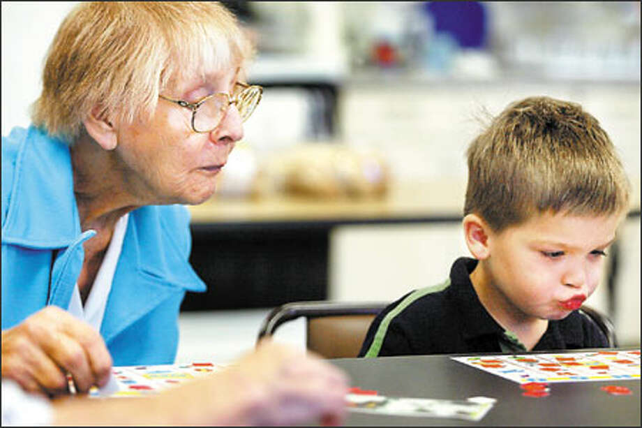 Volunteer Hazel Lyson looks at 4-year-old Blake LaBrash's bingo board as he figures out that he won the game at Whittier Elementary School. The mayor's budget allocates no money for School Programs Involving Community Elders, a program that connects senior citizens and youngsters. Photo: Karen Ducey, Seattle Post-Intelligencer / Seattle Post-Intelligencer