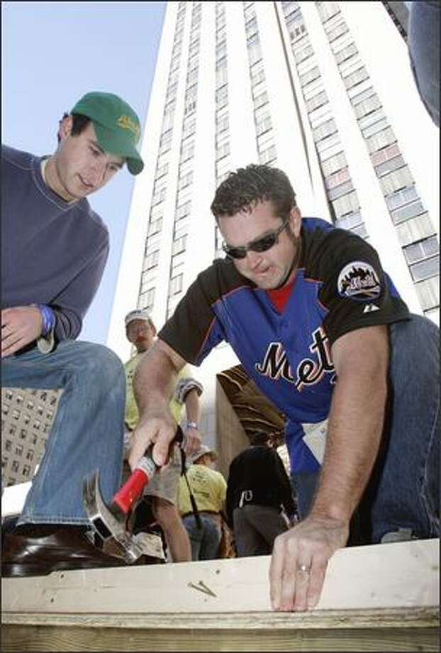 This is what we call a good use of muscle! Here we have New York Mets pitcher Heath Bell helping construct a home for victims of Hurricane Katrina (through Habitat for Humanity) at Rockefeller Center in New York. Hopefully, the volunteer overlooking his work is an expert, because, well, Bell may not be. Photo: Associated Press / Associated Press