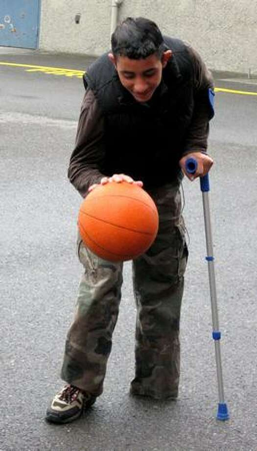 15-year-old Sobhi Subeh dribbles the basketball before dropping his crutch and making a basket. Sobhi was brought to the Seattle area from Gaza to receive a prosthetic leg. (Sharon Hong/seattlepi.com)