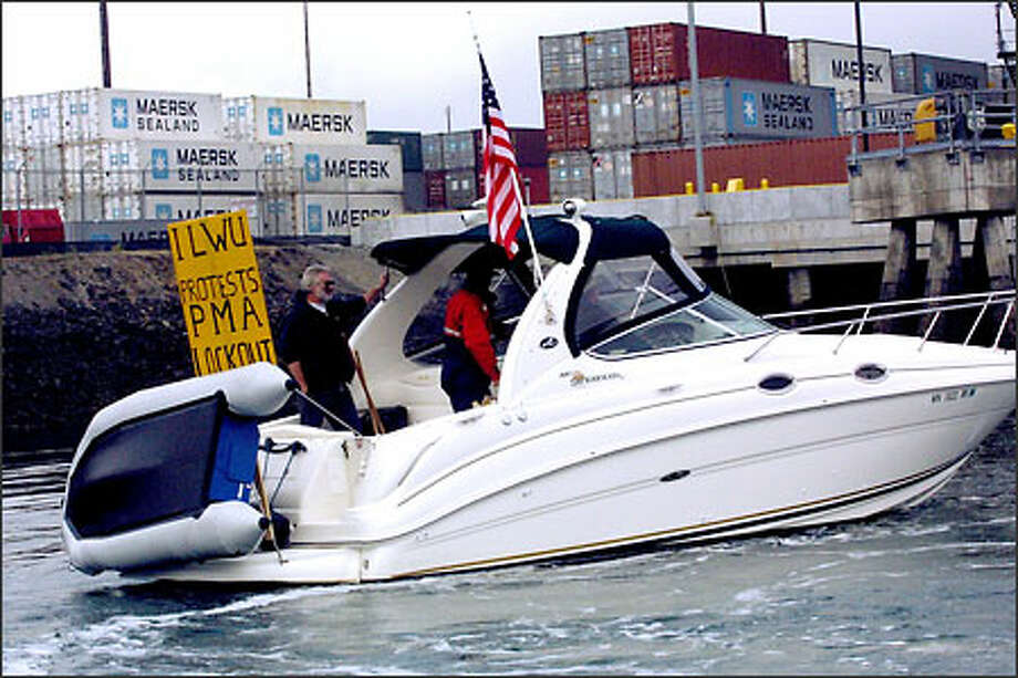 They cover the waterfront, in this case Longshore workers picketing by powerboat on the Sitcum Waterway in Tacoma yesterday. Unloaded cargo containers sit on the terminal behind them. Photo: Phil H. Webber, Seattle Post-Intelligencer / Seattle Post-Intelligencer