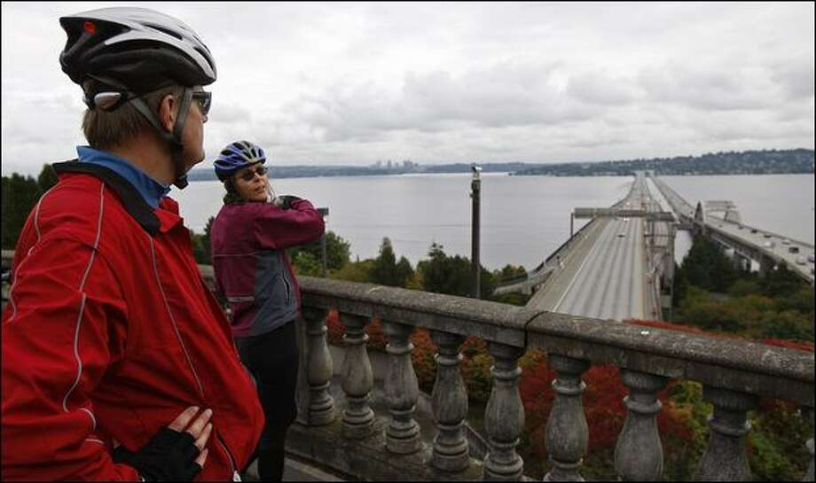 "Bill and Susie Thorness of Seattle look out over the I-90 floating bridge. Bill Thorness is the author of ""Biking Puget Sound: 50 Rides From Olympia to the San Juans."" Pedaling across the bridge is ""something everyone should do,"" Thorness says."