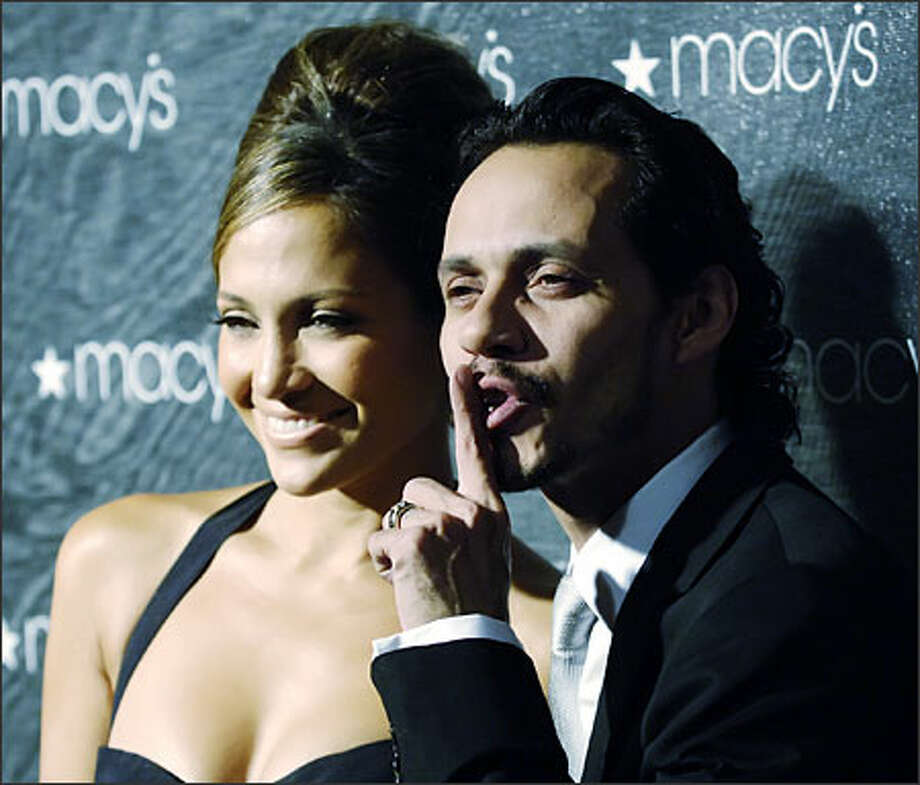"""Be quiet, or my wife will take away your first born and make him or her work in one of her sweatshops!"" says Marc Anthony. No, we jest. He's asking the adoring crowd to simmer down while Jennifer Lopez poses for photogs at Macy's Passport HIV/AIDS fund-raiser and fashion show at Santa Monica last week. Photo: Associated Press / Associated Press"