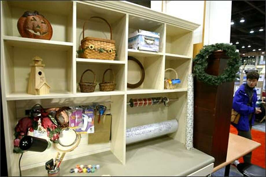 A craft center, complete with a chrome rod for bolts of ribbons, a backboard that can be hung with hooks for glue guns, scissors, tools, and numerous shelves and cubbyholes, is offered by Closets by Design. Photo: Scott Eklund, Seattle Post-Intelligencer / Seattle Post-Intelligencer