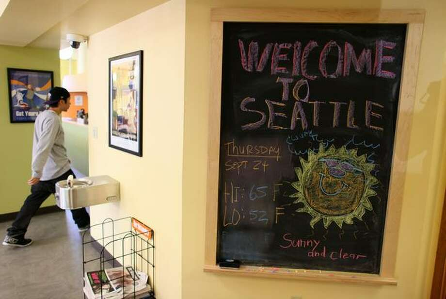 A guest walks past a board welcoming travelers to the new American Hotel, part of Hostelling International's network of low-cost rooms for travelers. The new hostel adds 320 beds for budget travelers in Seattle. Photo: Joshua Trujillo, Seattlepi.com / seattlepi.com