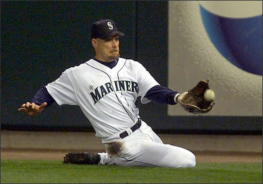 Mariners right fielder Jay Buhner makes a sliding catch on a fly ball hit by Texas Ranger Bill Haselman to end the fifth inning. The Rangers had runners at first and third, threatening to take the lead from the M's -- who went on to win 1-0 for their 116th game of the season. That matches an all-time record set by the 1906 Cubs. Photo: Dan DeLong, Seattle Post-Intelligencer / Seattle Post-Intelligencer