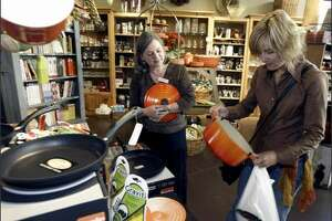 Michele Friedman, left, helps Barbara Haspedis at Mrs. Cook's, a University Village store that lets customers try before they buy.