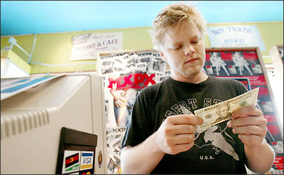 Troy Nelson takes a close look at a new $20 bill after he received it yesterday for the purchase of a CD at Easy Street Cd's & Tapes in Seattle Photo: Paul Joseph Brown, Seattle Post-Intelligencer / Seattle Post-Intelligencer