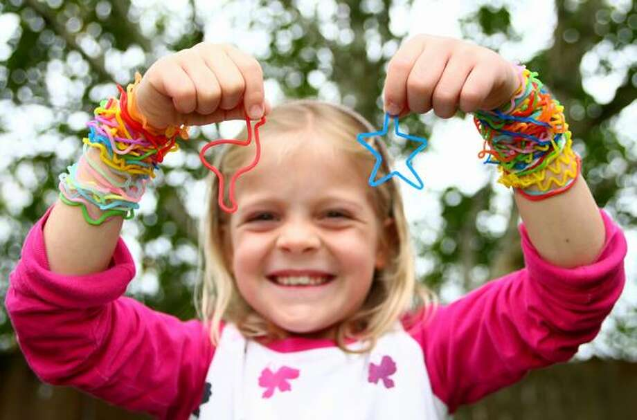 Second-grader Mary Farewell shows off some of her favorite Silly Bandz, silicone rubber bands that form shapes including letters, symbols and animals. The hugely popular and colorful bands are worn on the arms and are traded and collected by school-aged children. Photo: Joshua Trujillo, Seattlepi.com / seattlepi.com