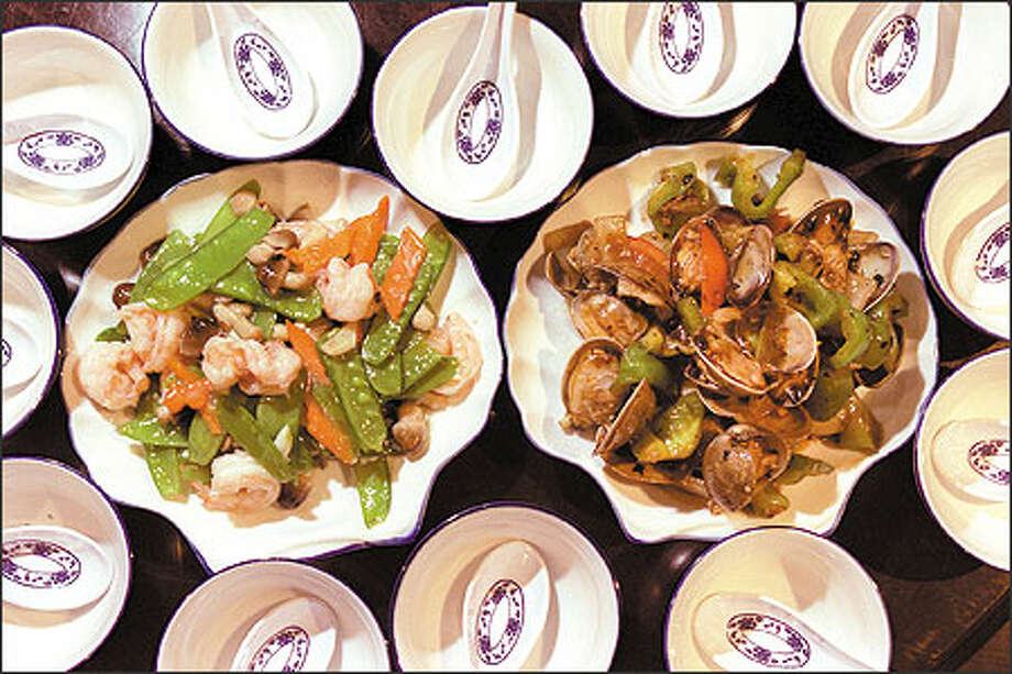 Prawns with Snow Peas, left, and Clams With Black Bean Sauce are among the entrees at the New Kowloon Seafood Restaurant at 900 S. Jackson St. in the International District. Photo: Loren Callahan, Seattle Post-Intelligencer / Seattle Post-Intelligencer