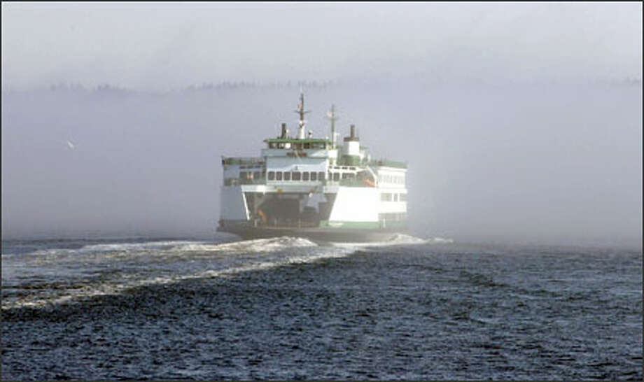 A ferry on the Mukilteo-Clinton run churns toward the fog. Once funding is figured out, the state would eventually like to construct a new dock at Mukilteo. Photo: Meryl Schenker, Seattle Post-Intelligencer / Seattle Post-Intelligencer