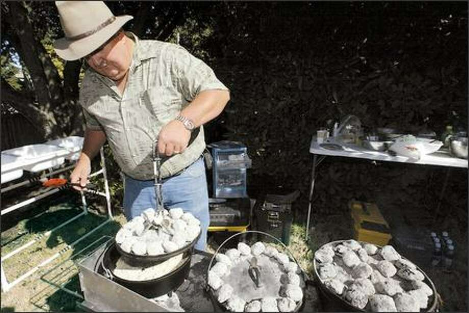 Dale Beam removes a lid covered with charcoal as he checks on chicken in his Dutch oven. Local enthusiasts have Dutch oven gatherings to cook and sample each other's recipes. They also cater events, do cooking demonstrations and give introductory classes. Photo: Jim Bryant, Seattle Post-Intelligencer / Seattle Post-Intelligencer