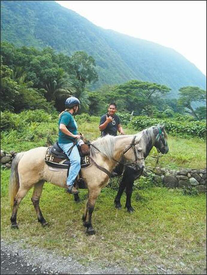 Guide Keoni Ah Puck, right, of Na'alapa Stables shares local lore with a guest. (Elizebeth Kaye McCall)