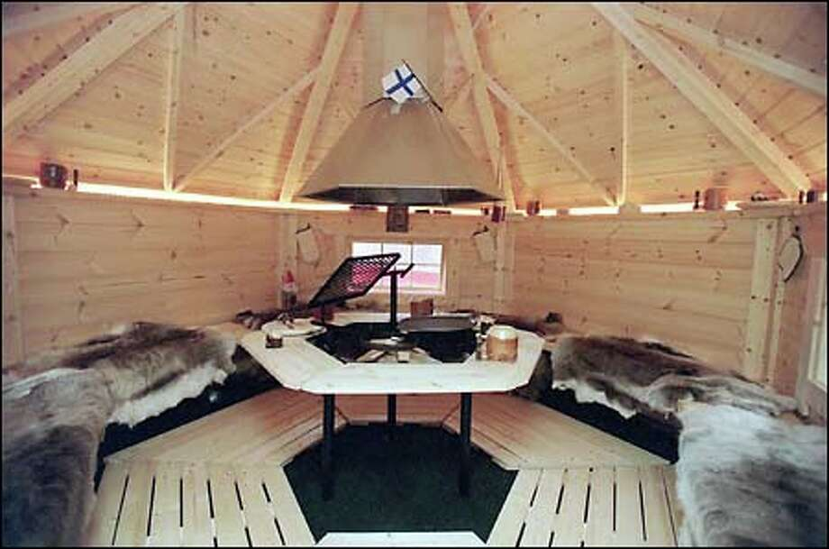 The Arctic Grillhouse comes complete with reindeer hides and wooden cutlery. The grill in the center burns wood or charcoal. Photo: Seattle Post-Intelligencer / Seattle Post-Intelligencer