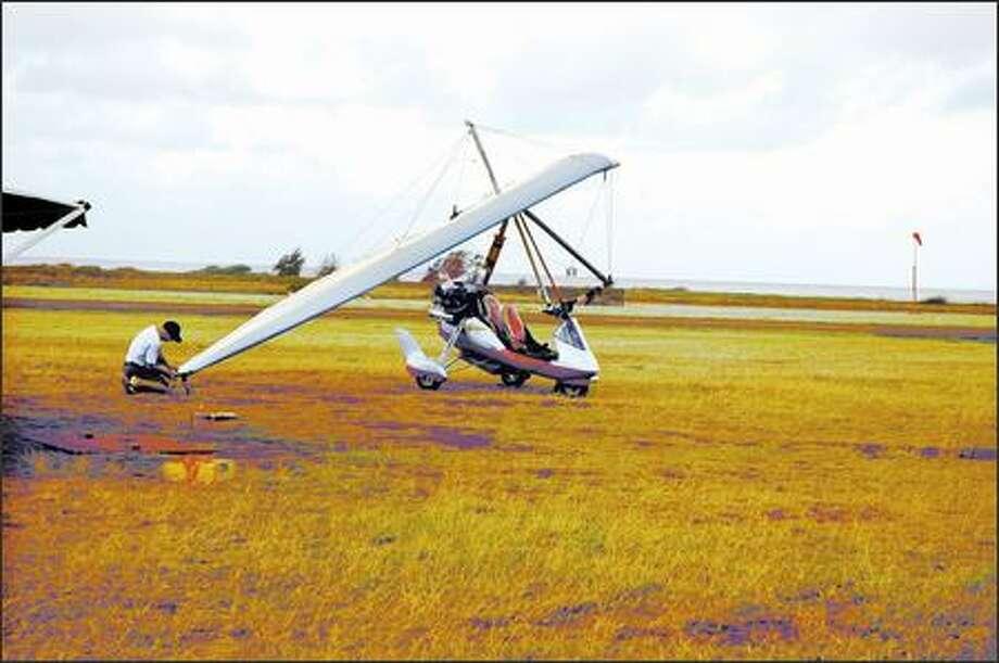 "Pilot Robert Combs prepares his ultralight ""trike"" for takeoff. (HERB KAVET)"