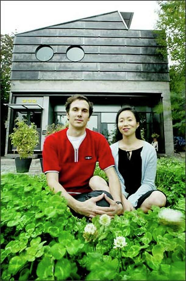 Daniel Mihalyo and Annie Han of Lead Pencil Studio built their concrete, steel and glass house and much of the furniture in the open, loftlike first floor and the second floor studio. The pair welded the oversize steel frame dominating their living room, which has a cineramic view of Seattle's skyline. Photo: Dan DeLong, Seattle Post-Intelligencer / Seattle Post-Intelligencer